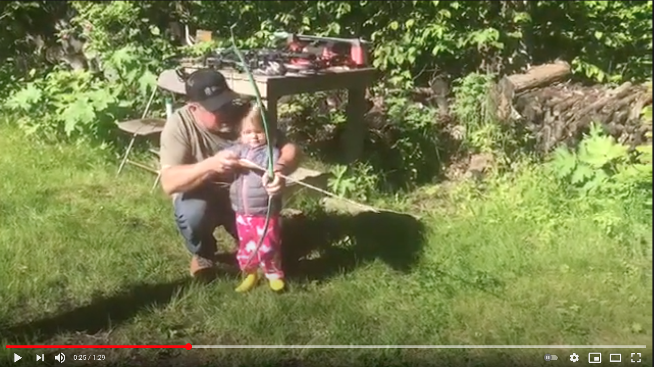Brad Fenson teaches a young child how to shoot a bow for the first time